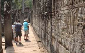 The tourist with a bas-relief statue of Khmer Culture in Angkor Wat, Cambodia