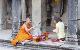 Buddhist monk give a wish to people in Angkor Wat